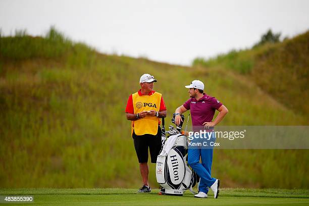 Tyrrell Hatton of England and his caddie Kyle Roadley prepare to play a shot on the 15th hole during the first round of the 2015 PGA Championship at...