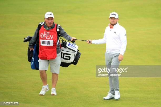 Tyrrell Hatton of England and his caddie Mick Donaghy look on the 2nd hole during the first round of the 148th Open Championship held on the Dunluce...