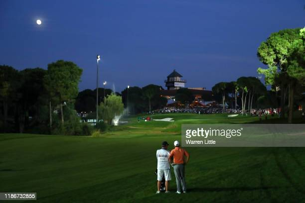 Tyrrell Hatton of England and his caddie Mick Donaghy prepare to play an approach shot on the eighteenth in the fourth playoff hole during Day Four...