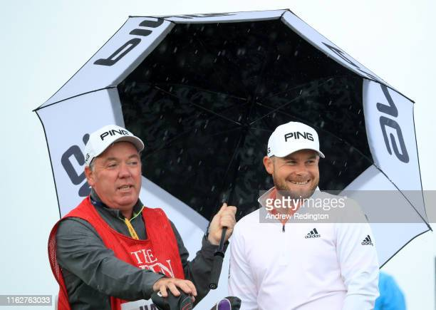 Tyrrell Hatton of England and his caddie Mick Donaghy shelter under an umbrella on the 3rd hole during the first round of the 148th Open Championship...