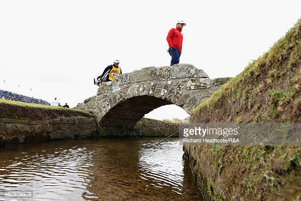 Tyrrell Hatton of England and his caddy Kyle Roadley walk over Swilcan Bridge with their caddies during the first round of the 144th Open...