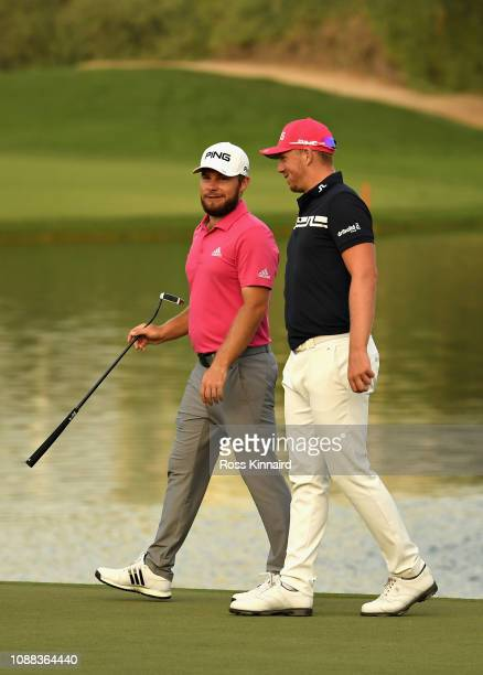 Tyrrell Hatton of England and Matt Wallace of England talk on hole eighteen during Day Two of the Omega Dubai Desert Classic at Emirates Golf Club on...