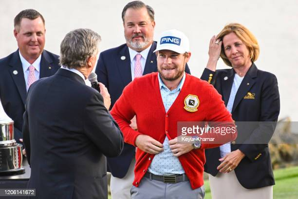 Tyrrell Hatton of England buttons up the winner's cardigan following his one stroke victory in the final round of the Arnold Palmer Invitational...