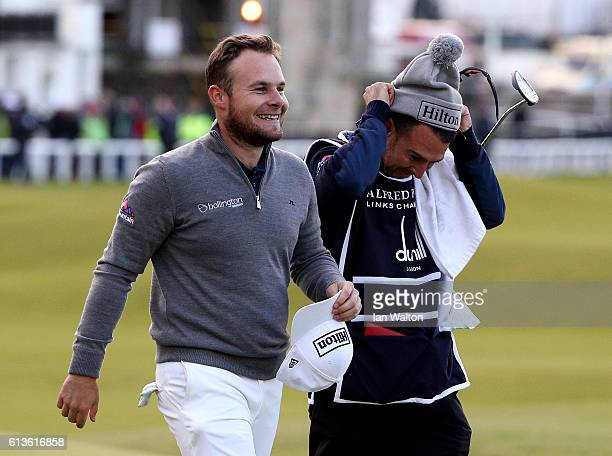 Tyrrell Hatton of England celebrates with his caddie Chris Rice after victory on the 18th green during the final round of the Alfred Dunhill Links...