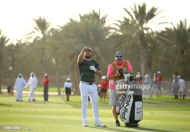 Tyrrell Hatton of England checks the wind direction for his third shot on the 18th hole during the final round of the Abu Dhabi HSBC Championship at...