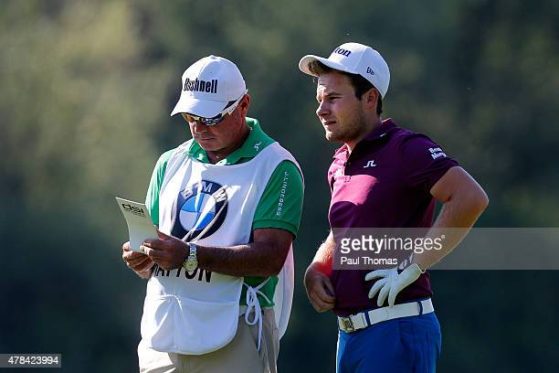 Tyrrell Hatton of England discusses a shot with his caddie during the BMW International Open day one at the Eichenried Golf Club on June 25 2015 in...