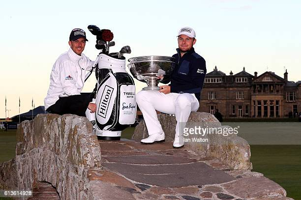 Tyrrell Hatton of England holds the trophy aloft with his caddie Chris Rice on the Swilken Bridge on the 18th hole after winning the Alfred Dunhill...