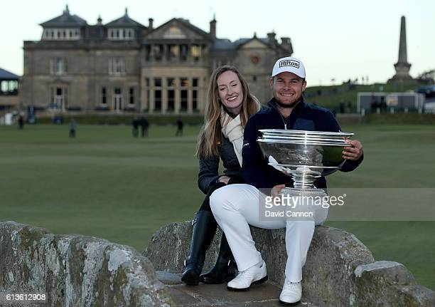 Tyrrell Hatton of England holds the trophy aloft with his girlfriend Emily Braisher on the Swilken Bridge on the 18th hole after winning the Alfred...