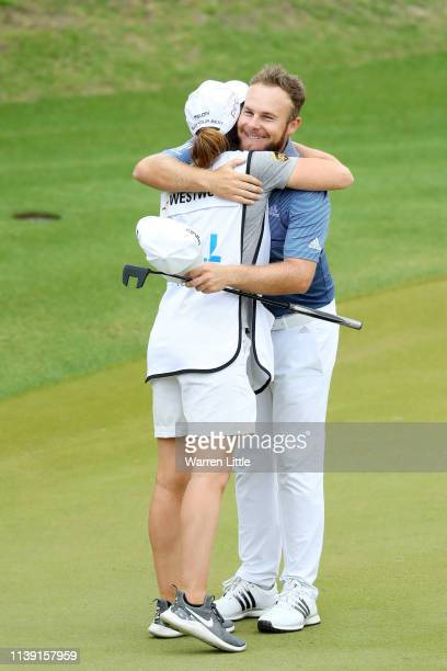 Tyrrell Hatton of England hugs the girlfriend and caddie of Lee Westwood of England Helen Storey after their match during the third round of the...