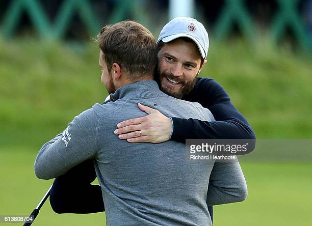 Tyrrell Hatton of England is congratulated by his playing partner Jamie Dornan after victory on the 18th green during the final round of the Alfred...
