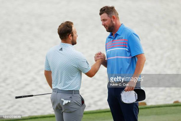 Tyrrell Hatton of England is congratulated by Marc Leishman of Australia on the 18th green after winning during the final round of the Arnold Palmer...