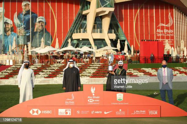 Tyrrell Hatton of England is presented with the trophy alongside Abdulfattah Al Sharaf, Group General Manager & CEO HSBC UAE, Aref Al Awani, General...