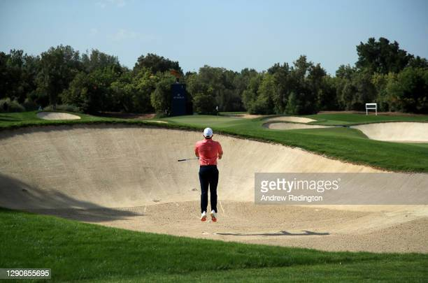 Tyrrell Hatton of England jumps to see out of a bunker on the 1st hole during Day Two of the DP World Tour Championship at Jumeirah Golf Estates on...
