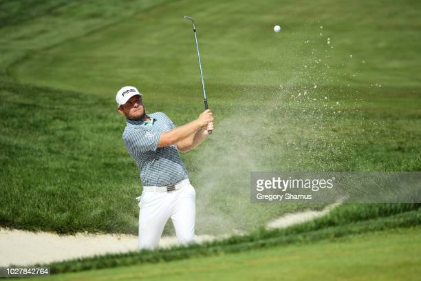 Tyrrell Hatton of England plays a shot from a bunker on the 12th hole during the first round of the BMW Championship at Aronimink Golf Club on...