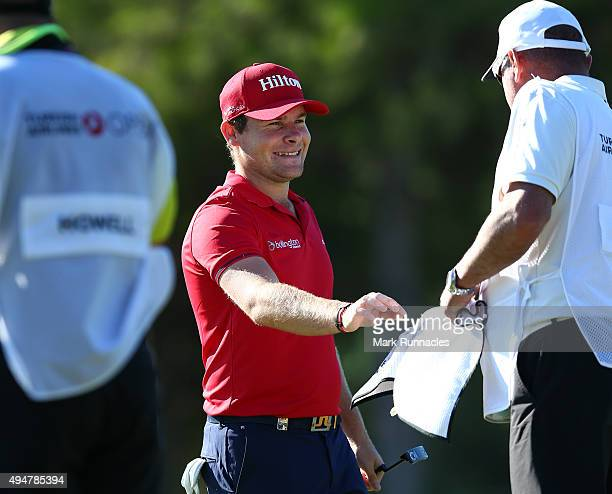 Tyrrell Hatton of England plays celebrates with his caddie after chipping in for and eagle on the second during the first round of the Turkish...