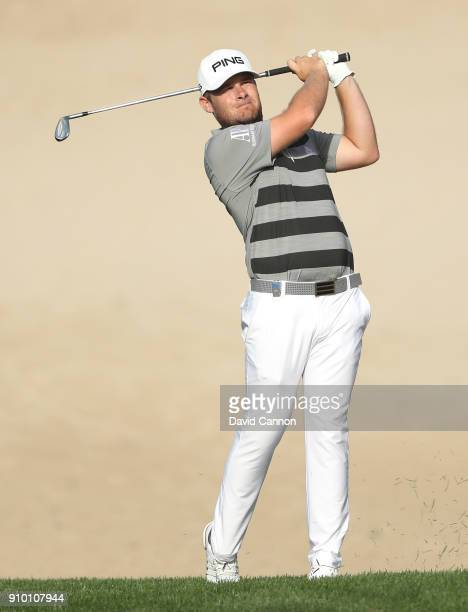 Tyrrell Hatton of England plays his second shot on the par 414th hole during the first round of the Omega Dubai Desert Classic on the Majlis Course...