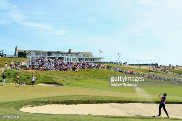 Tyrrell Hatton of England plays his third shot from a bunker on the 18th hole during the final round of the 2018 US Open at Shinnecock Hills Golf...