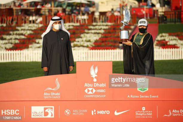 Tyrrell Hatton of England poses for a photograph with the trophy alongside Aref Al Awani, General Secretary of Abu Dhabi Sports Council following...