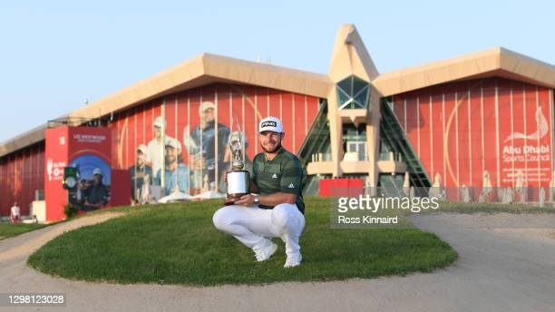 Tyrrell Hatton of England poses for a photograph with the trophy following victory during Day 4 of the Abu Dhabi HSBC Championship at Abu Dhabi Golf...