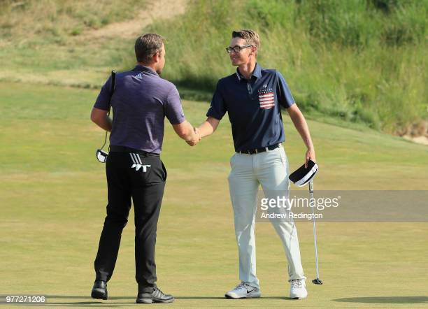 Tyrrell Hatton of England shakes hands with Dylan Meyer of the United States on the 18th green during the final round of the 2018 US Open at...
