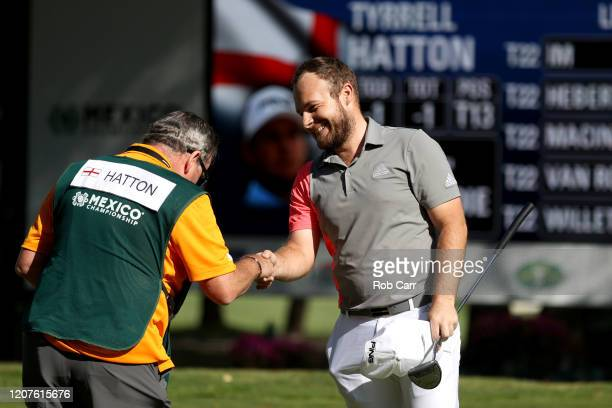 Tyrrell Hatton of England shakes hands with his caddie Mick Donaghy on the 18th green during the first round of the World Golf Championships Mexico...