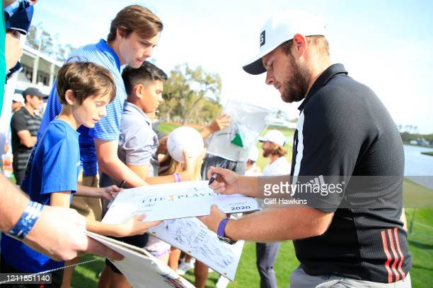 Tyrrell Hatton of England signs his autograph for fans during a practice round prior to The PLAYERS Championship on The Stadium Course at TPC...