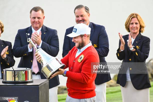 Tyrrell Hatton of England smiles as he holds the trophy following his one stroke victory in the final round of the Arnold Palmer Invitational...