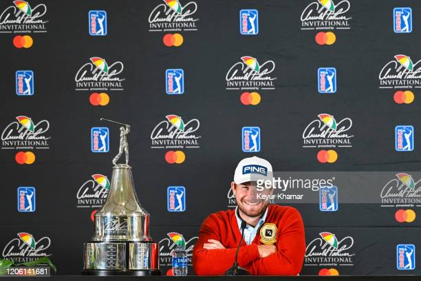 Tyrrell Hatton of England smiles next to the trophy during a press conference following his one stroke victory in the final round of the Arnold...