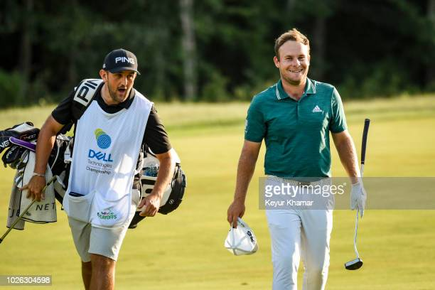 Tyrrell Hatton of England smiles with his caddie after nearly holing out for eagle on the 18th hole fairway during the third round of the Dell...