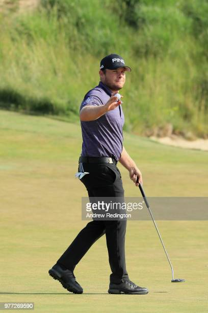 Tyrrell Hatton of England waves after putting on the 18th green during the final round of the 2018 US Open at Shinnecock Hills Golf Club on June 17...