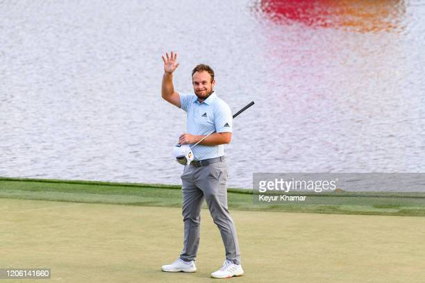 Tyrrell Hatton smiles and waves to fans as he celebrates his one stroke victory on the 18th hole green during the final round of the Arnold Palmer...