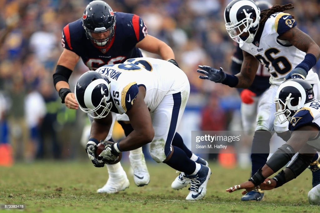 Tyrunn Walker #95 of the Los Angeles Rams recovers a fumble as Nick Martin #66 of the Houston Texans tackles him during the second half of game at Los Angeles Memorial Coliseum on November 12, 2017 in Los Angeles, California.
