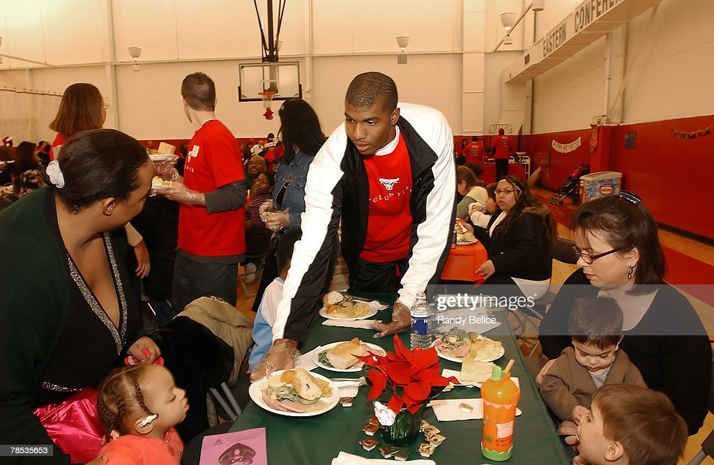 Tyrus Thomas of the Chicago Bulls serves a meal to a family