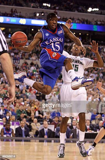 Tyshawn Taylor of the Kansas Jayhawks looks to pass the ball in midair against Durrell Summers of the Michigan State Spartans during the third round...