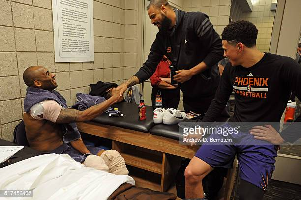 Tyson Chandler and Devin Booker of the Phoenix Suns talk to Kobe Bryant of the Los Angeles Lakers after the game in the locker room on March 23 2016...
