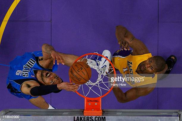 Tyson Chandler of the Dallas Mavericks dunks the ball over his head as Ron Artest of the Los Angeles Lakers looks on in the first quarter of Game One...
