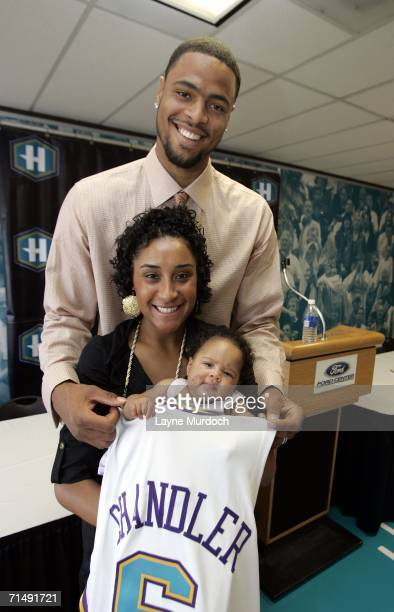 Tyson Chandler of the New Orleans/Oklahoma City Hornets wraps his new jersey around wife Kimberly and twomonthold daughter SachaMarie after a press...
