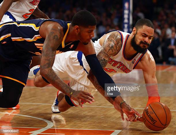 Tyson Chandler of the New York Knicks dives for the ball against Paul George of the Indiana Pacers during Game Five of the Eastern Conference...