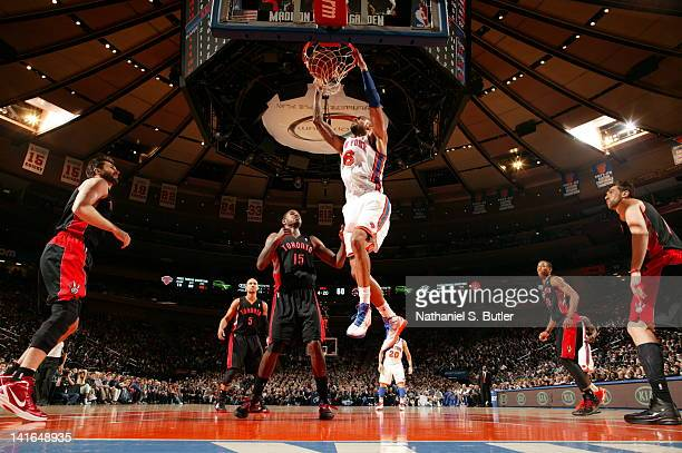 Tyson Chandler of the New York Knicks hangs on the rim after a dunk against Amir Johnson of the Toronto Raptors during the game on March 20 2012 at...