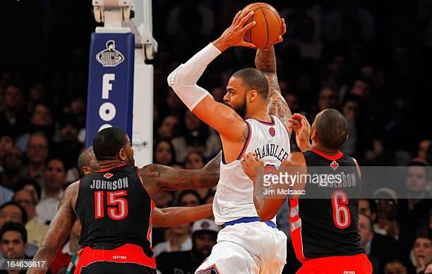 Tyson Chandler of the New York Knicks in action against Amir Johnson and Alan Anderson of the Toronto Raptors at Madison Square Garden on February 13...