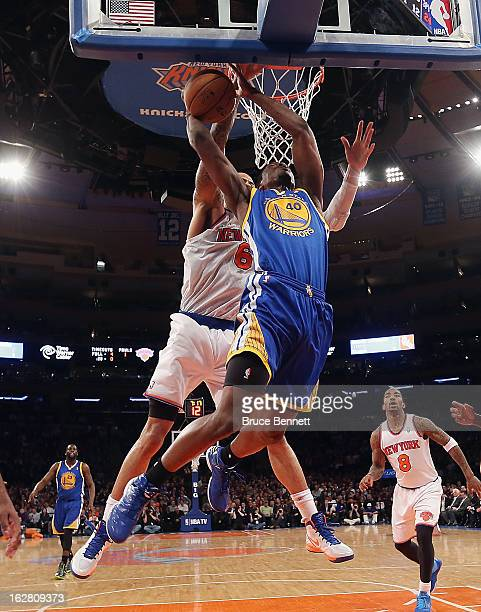 Tyson Chandler of the New York Knicks reaches from behind and blocks at shot by Harrison Barnes of the Golden State Warriors at Madison Square Garden...