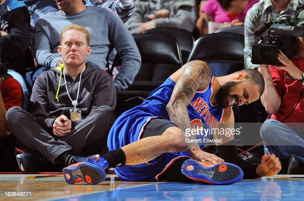 Tyson Chandler of the New York Knicks reacts after bruising his knee during play against the Denver Nuggets on March 13 2013 at the Pepsi Center in...