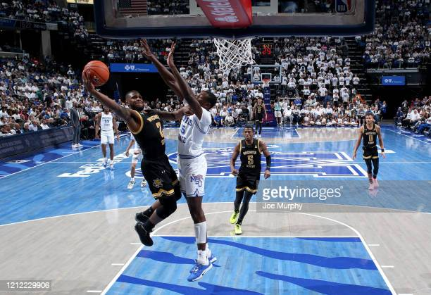 Tyson Etienne of the Wichita State Shockers drives to the basket for a layup against Lance Thomas of the Memphis Tigers during a game on March 5 2020...