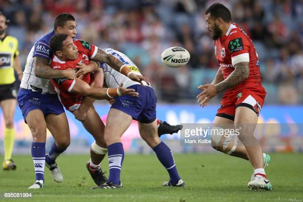 Tyson Frizell sd passes as he is tackled by Michael Lichaa and Josh Jackson of the Bulldogs during the round 14 NRL match between the Canterbury...