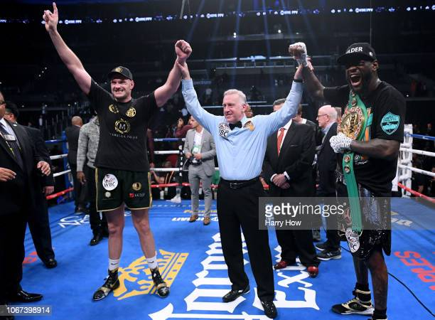 Tyson Fury and Deontay Wilder pose for a photo with referee Jack Reiss after fighting to a draw during the WBC Heavyweight Championship at Staples...