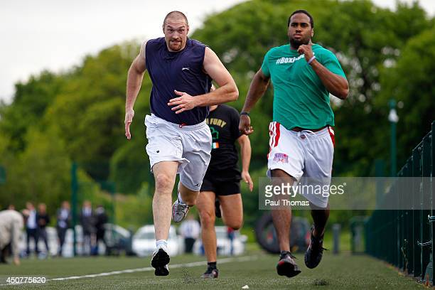 Tyson Fury and Eddie Chambers run during the Tyson Fury Media Session at the Eddie Davies Football Academy on June 17 2014 in Bolton England