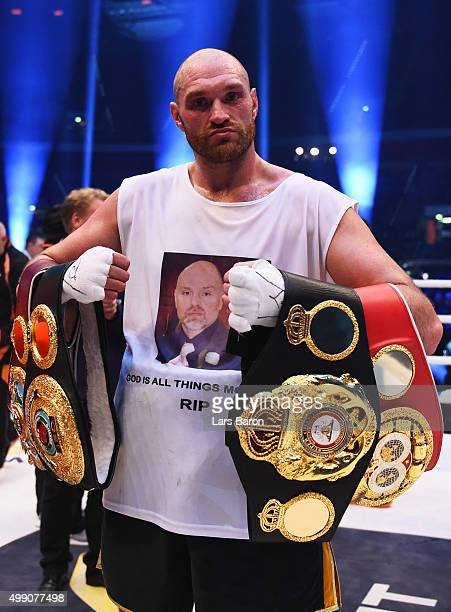 Tyson Fury celebrates with title belts as he defeats Wladimir Klitschko to become new World Heavyweight Champion after the IBF IBO WBA WBO...