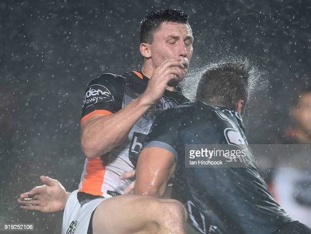 Tyson Gamble of the Tigers is hit by Sam Hoare of the Cowboys during the NRL trial match between the North Queensland Cowboys and the Wests Tigers at...