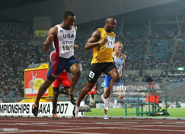 Tyson Gay of the United States of America comes in ahead of third placed Asafa Powell of Jamaica to win the Men's 100m final on day two of the 11th...
