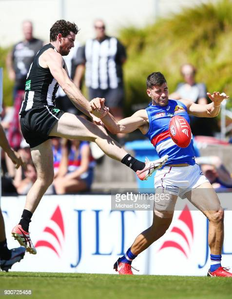 Tyson Goldsack of the Magpies and Marcus Adams of the Bulldogs compete for the ball during the JLT Community Series AFL match between Collingwood...